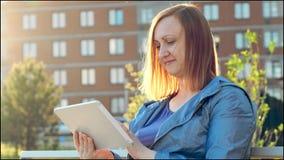 Kvinna som använder minnestavladatoren som sitter på bänk i stad lager videofilmer