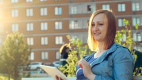 Kvinna som använder minnestavladatoren som sitter på bänk i stad arkivfilmer