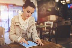 Kvinna som använder minnestavlan i kafé arkivbild