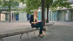 Kvinna som använder minnestavlan på bänk Formellt affärskvinnasammanträde på uteplats för bänk i regeringsställning och bläddrami arkivfilmer