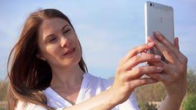 Kvinna som använder mobilen mot blå himmel Le kvinnlign som tar selfiefotoet på mobiltelefonen i ultrarapid arkivfilmer