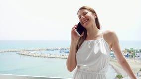 Kvinna som använder mobilen på balkong Kvinnlig på semester som talar med vännen via mobiltelefonen i ultrarapid stock video