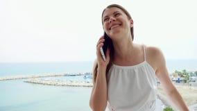 Kvinna som använder mobilen på balkong Kvinnlig på semester som talar med vännen via mobiltelefonen i ultrarapid lager videofilmer