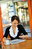 Kvinna som använder mobiltelefon på cafen Arkivfoton