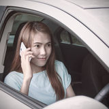 Kvinna som använder mobiltelefonen i bilen Arkivbild
