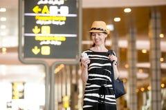 Kvinna som använder mobiltelefonen i flygplats arkivbild