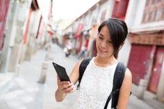 Kvinna som använder mobiltelefonen i Rua da felicidade Royaltyfria Bilder