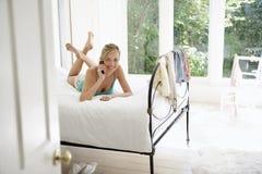 Kvinna som använder mobiltelefonen i säng Royaltyfria Foton