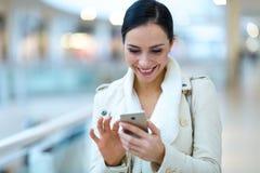 Kvinna som använder mobiltelefonen i shoppinggalleria Fotografering för Bildbyråer