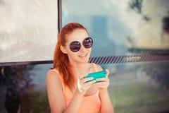 Kvinna som använder mobiltelefonen i station royaltyfri bild
