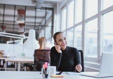 Kvinna som använder mobiltelefonen medan på arbete Royaltyfri Bild