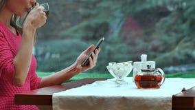 Kvinna som använder mobiltelefonen och dricker te i kafé Royaltyfri Bild