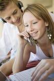 Kvinna som använder mobiltelefonen och mannen med hörlurar Royaltyfria Bilder