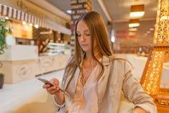 Kvinna som använder mobiltelefonen på kafét Royaltyfri Fotografi