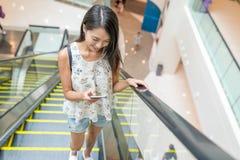 Kvinna som använder mobiltelefonen på rulltrappan Royaltyfri Fotografi