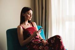 Kvinna som använder mobiltelefonen på soffan vid fönstret royaltyfri foto