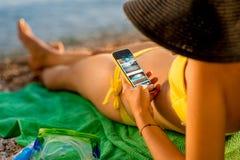 Kvinna som använder mobiltelefonen på stranden arkivfoto