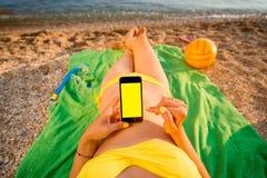 Kvinna som använder mobiltelefonen på stranden arkivfoton