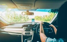 Kvinna som använder navigering app på smartphonen, medan köra en bil Arkivfoto