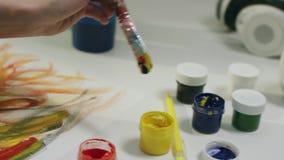 Kvinna som använder olika färger för att dra med borsten arkivfilmer