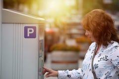 Kvinna som använder parkeringsmetern Royaltyfri Foto