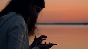 Kvinna som använder Smartphone på solnedgången lager videofilmer