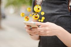 Kvinna som använder smartphonen som överför emojis fotografering för bildbyråer
