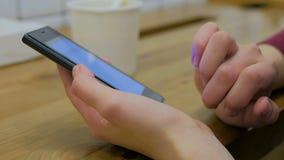 Kvinna som använder smartphonen i kafé Fotografering för Bildbyråer