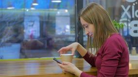 Kvinna som använder smartphonen i kafé Royaltyfri Fotografi
