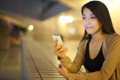 Kvinna som använder smartphonen i stad arkivfoto
