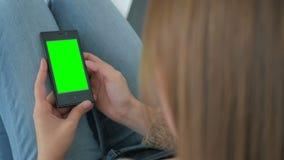 Kvinna som använder smartphonen med den gröna skärmen Arkivbilder