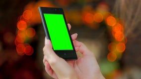 Kvinna som använder smartphonen med den gröna skärmen Royaltyfria Bilder