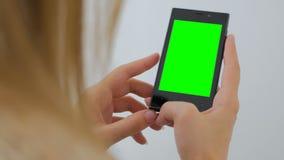 Kvinna som använder smartphonen med den gröna skärmen Arkivbild
