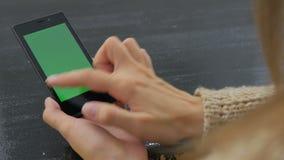 Kvinna som använder smartphonen med den gröna skärmen lager videofilmer