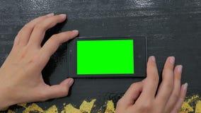 Kvinna som använder smartphonen med den gröna skärmen Arkivfoto