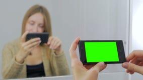 Kvinna som använder smartphonen med den gröna skärmen Royaltyfri Bild