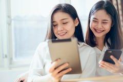 Kvinna som använder smartphonen och minnestavlan på internetlivsstilen royaltyfria foton
