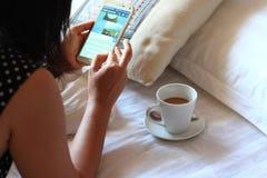 Kvinna som använder smartphonen på säng Royaltyfri Foto
