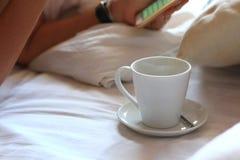 Kvinna som använder smartphonen på säng Arkivfoto