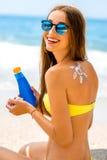 Kvinna som använder solkräm på stranden royaltyfri bild