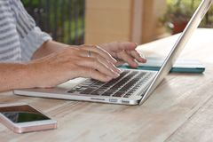 Kvinna som använder teknologi, en bärbar datordator, närbild av händer arkivfoton