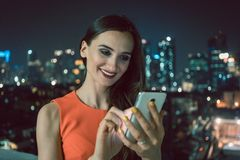 Kvinna som använder telefonen för socialt massmedia i stads- inställning royaltyfria bilder