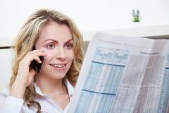 Kvinna som använder telefonen, medan läsa fotografering för bildbyråer