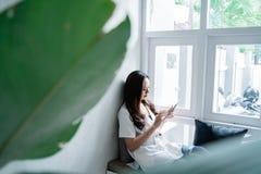 Kvinna som anv?nder hennes grej, medan sitta i kaf? royaltyfri fotografi