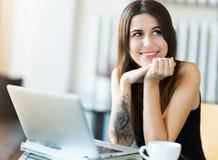 Kvinna som använder bärbara datorn på kafét Arkivbild