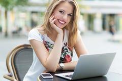 Kvinna som använder bärbara datorn på kafét Arkivfoto