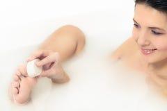 Kvinna som använder en polermedelsten för att exfoliate hennes fot Arkivbild