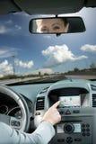 Kvinna som använder gps-navigatören i en bil Arkivfoto