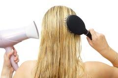 Kvinna som använder hårtork och hårkammen Royaltyfri Bild