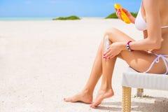 Kvinna som använder sunscreen på stranden Royaltyfri Foto